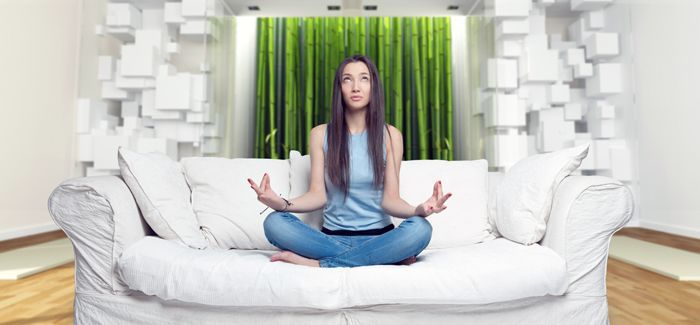 Young woman sitting on a sofa in the lotus position meditating i