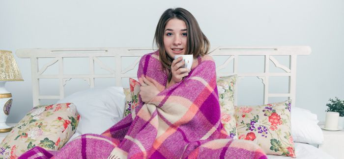Sick woman covered with blanket holding cup of tea
