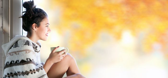 Young beautiful brunette woman with cup of coffee wearing knitt