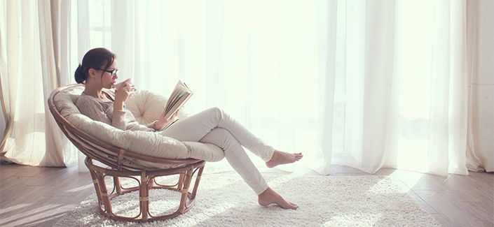 Young woman at home sitting on modern chair in front of window r